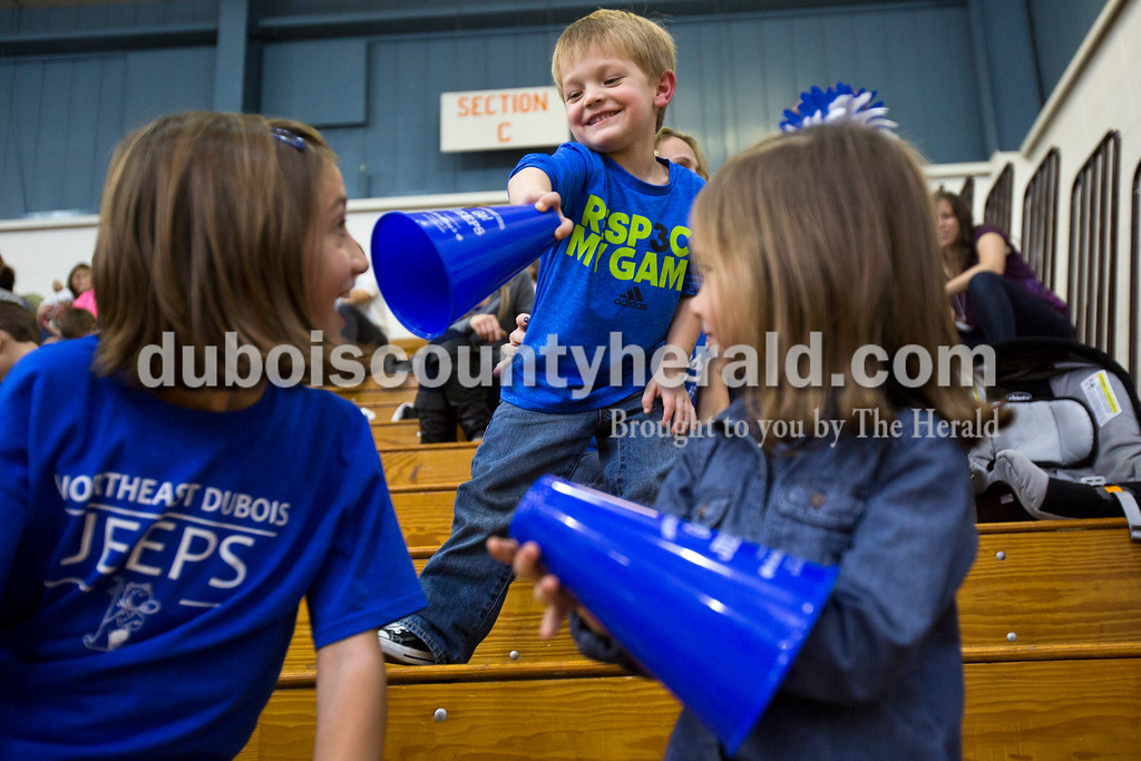 Alisha Jucevic/The Herald<br /> Northeast Dubois fans Kenzie Cave of Dubois, 8, Tucker Woolems of Dubois, 4, and Hadley Denu of Huntingburg, 4, played together in the stands during Saturday night's game against Tecumseh in Dubois. The Jeeps won 53-46.