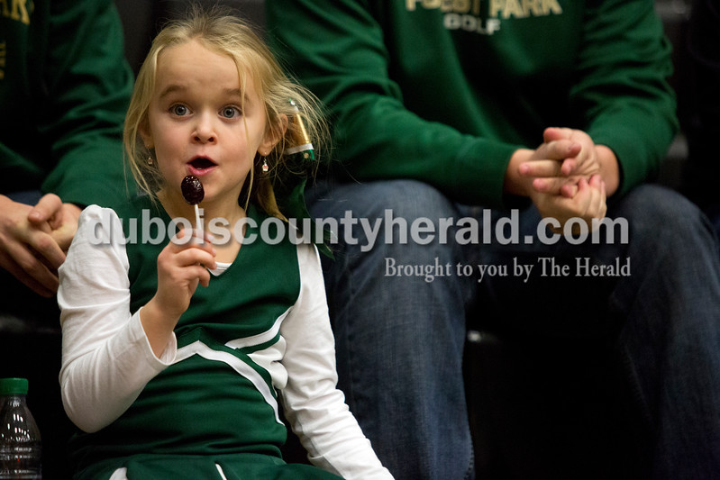 "Erica Lafser/The Herald<br /> Forest Park's head coach Jeff Litherland's daughter, Layni of Troy, 6, watched Saturday night's Dubois County Hoops Classic consolation game against Southridge in Jasper. ""(My cheerleading costume) is green and the Rangers are green,"" Layni said. The Rangers won 57-48."