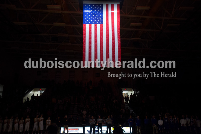Erica Lafser/The Herald<br /> Jasper's and Northeast Dubois' boys basketball teams lined up and honored the flag for the playing of the national anthem before Saturday night's Dubois County Hoops Classic championship game in Jasper. The Wildcats won 60-31.