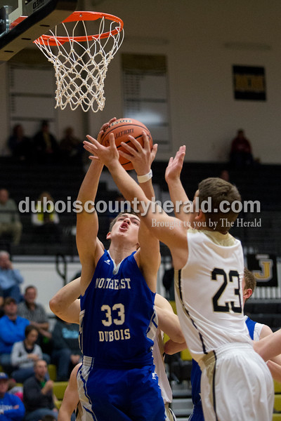 Erica Lafser/The Herald<br /> Northeast Dubois' Scott Betz vied for a rebound with Jasper's Hunter Gossett during Saturday night's Dubois County Hoops Classic championship game in Jasper. The Wildcats won 60-31.