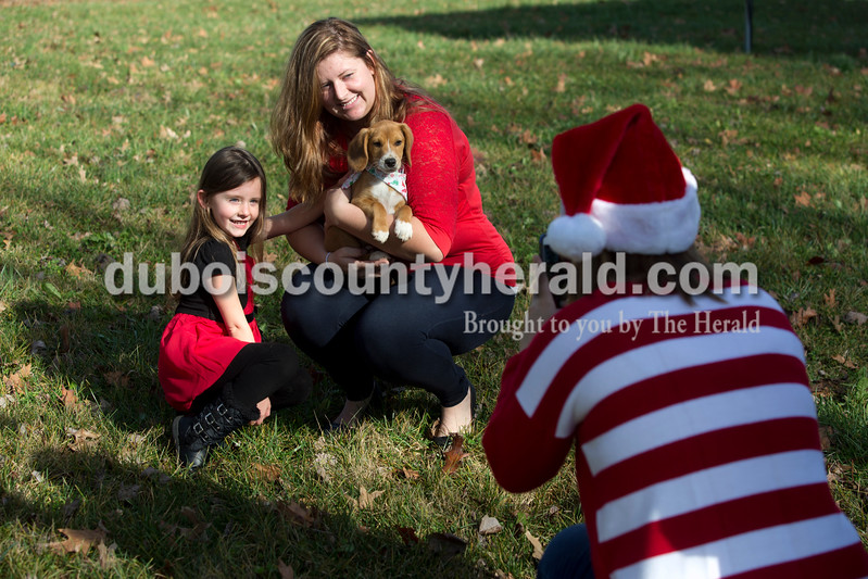 "Erica Lafser/The Herald<br /> Dubois County Humane Society adoption counselor Hannah Fuhs of Jasper, right, took a photo of Delilah, left, 4, and her mom Ashton Stivers of Huntingburg with their new 8 week old puppy, Kale, in their backyard in Huntingburg on Thursday. Fuhs delivered Kale to their home on Christmas Eve in a box to surprise Delilah with him for a Christmas present. ""(Delilah's) been asking for a dog since her birthday in April"" Ashton said. Despite the Humane Society offering this surprise to everyone, the Stivers were the only family who accepted the offer."