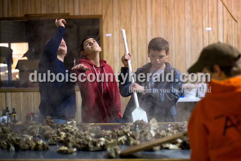 Alisha Jucevic/The Herald<br /> Cordell Padgett of Loogootee, 13, left, and Kaleb Lawson of Jasper, 14, looked up at the steam rising from the meat bones as Joshua Schoenbachler of Jasper, 12, and Blake Danzer of Jasper, 12, spread the meat out on the table. St. Joe's Boy Scout troop 182 met on Saturday at Hedinger Roofing in Jasper to cook 100 gallons of mock turtle soup and 50 gallons of chili soup. Proceeds will go toward troop funds, including a summer trip to the Grand Canyon.