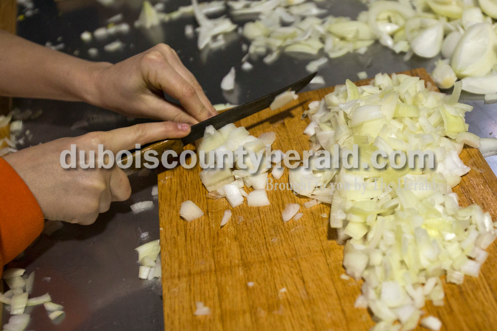 Alisha Jucevic/The Herald<br /> Blake Danzer of Jasper, 12, cut 50 pounds of onions with his fellow troop members during a fundraiser for the St. Joe's Boy Scouts troop 182 on Saturday at Hedinger Roofing in Jasper.