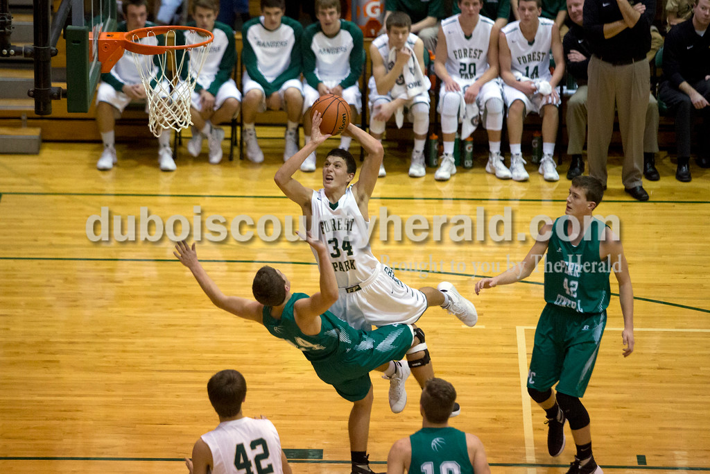 Forest Park's Ben Englert shot the ball as Perry Central's Lane Lynch drew a charge during Monday night's game in Ferdinand. The Rangers won 58-37. Ariana van den Akker/The Herald