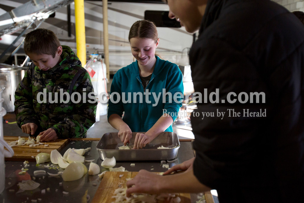 Alisha Jucevic/The Herald<br /> Kaitlin Albrecht of Jasper 14, center, chatted with Logan Hostetter of Jasper, 12, left, and Nick Hedinger of Jasper, 16, as they chopped 50 pounds of onions. St. Joe's Boy Scout troop 182 and their family members met on Saturday at Hedinger Roofing in Jasper to cook 100 gallons of mock turtle soup and 50 gallons of chili soup. Proceeds will go toward troop funds, including a summer trip to the Grand Canyon.