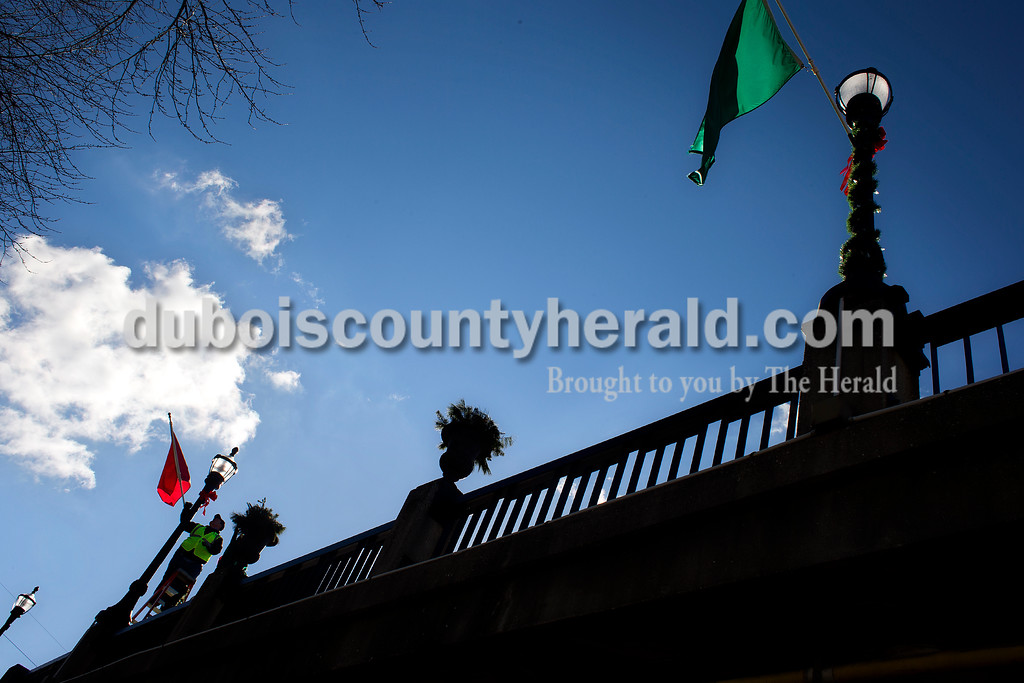 Dave Weatherwax/The Herald<br /> Jasper Municipal Electric Utility workers Jim Scherle and Larry Matheis, not pictured, removed the Christmas decorations and red and green flags from the lamp posts on the Third Avenue bridge that runs over the Patoka River in Jasper on Monday afternoon. The two were among several crew members scattered around the city taking down seasonal decorations during the day.
