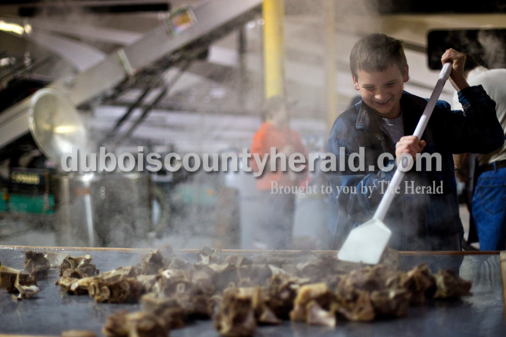 Alisha Jucevic/The Herald<br /> Joshua Schoenbachler of Jasper, 12, spread soup bones out on a table to be processed. St. Joe's Boy Scout troop 182 and their family members met on Saturday at Hedinger Roofing in Jasper to cook 100 gallons of mock turtle soup and 50 gallons of chili soup. Proceeds will go toward troop funds, including a summer trip to the Grand Canyon.