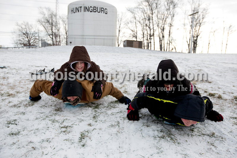 Ariana van den Akker/The Herald<br /> Raya Dollaway of Huntingburg, 10, top left, and her sister Rachel, 12, hopped onto their brothers Brett, 16, left, and Brandon, 14, to race down the hill at Niehaus Memorial Park in Huntingburg on Monday morning. All Dubois County schools were closed because of the snow and ice on Monday, though the siblings still had school in the afternoon because they are home schooled.