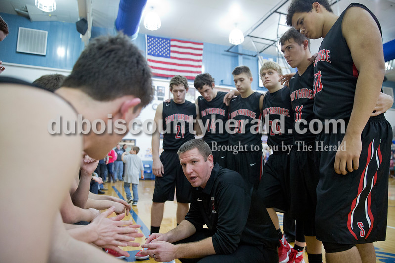 Sarah Ann Jump/The Herald<br /> Southridge head coach Ted O'Brien, center, talked to his team during a timeout at Saturday's game in Dubois. The Raiders won 56-48.