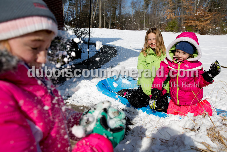 Karrigen Green, 10, got hit with a snowball thrown by Madi Wineinger, 7, right, as Lyllee Schnell, 9, laughed near their homes in the Woodland Hills neighborhood of Celestine on Tuesday.