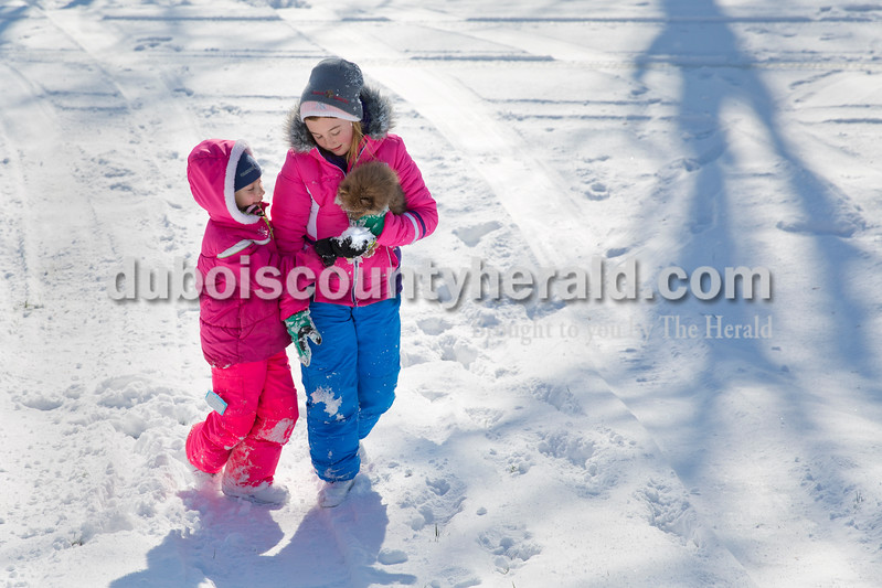 Karrigen Green, 10, right, carried her dog Pixie as her neighbor Madi Wineinger, 7, both of Celestine, tried to feed the dog snow near their homes in the Woodland Hills neighborhood of Celestine on Tuesday.