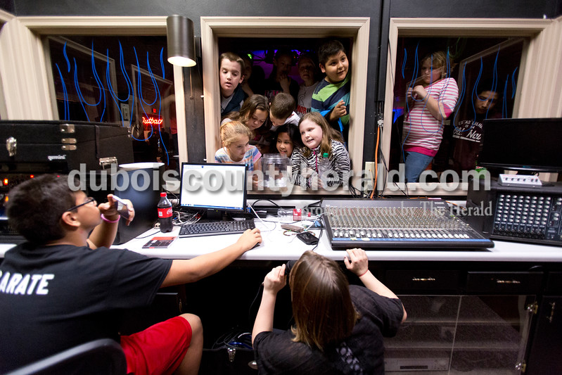 "Sarah Ann Jump/The Herald<br /> Kids piled into the window to the DJ booth to talk to Junior Zarate, 14, left, and Megan Stutsman, 15, both of Huntingburg, after the DJs gave away a prize to the first person to guess a song's title and artist during a ""crazy sock"" themed party for third through fifth graders at Teen Outback in Huntingburg on Friday. The party included dancing, games, dodgeball, video games, arcade games and other activities."