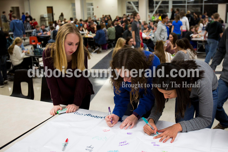 Alisha Jucevic/The Herald<br /> Jasper High School freshman, Megan Stiles, left, Zoe Biggs, and Carmina Armstrong, sign their name to accept Rachel's Challenge. This program is based upon the life and writings of Rachel Joy Scott, who was the first victim of the Columbine school shootings in 1999. The five goals of Rachel's Challenge are: look for the best in others, dream big, choose positive influences, speak with kindness and start your own chain reaction. By spreading kindness, respect and compassion, Rachel's Challenge strives to positively impact the lives of students and community members around the country.