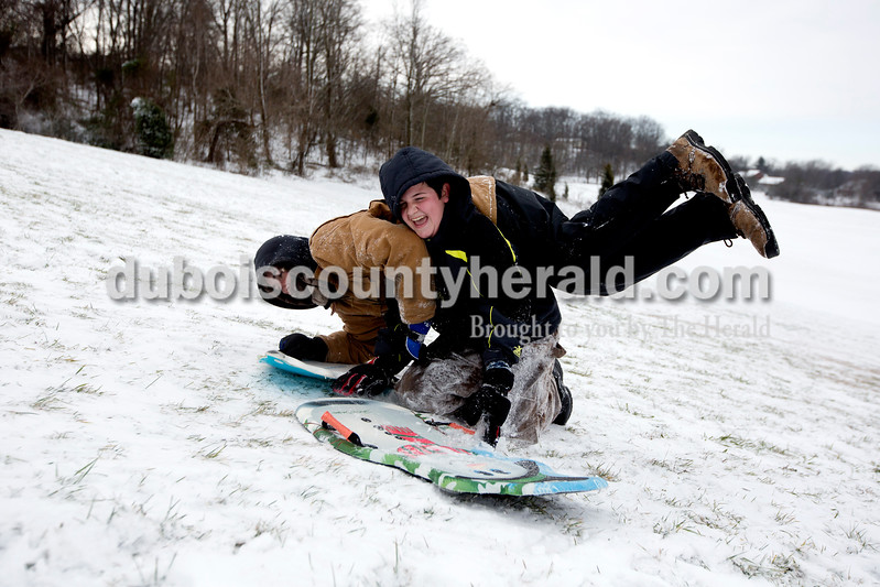 Ariana van den Akker/The Herald<br /> Brett Dollaway of Huntingburg, 16, left, purposely crashed into his brother Brandon, 14, while sledding at Niehaus Memorial Park in Huntingburg on Monday morning. All Dubois County schools were closed because of the snow and ice on Monday, though the brothers still had school in the afternoon because they are home schooled.