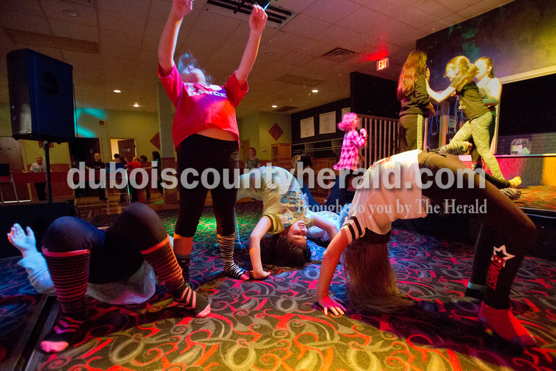 "Sarah Ann Jump/The Herald<br /> From left to right, Kaitlyn Barkley of Huntingburg, 9, Kara Schimitt of Holland, 8, Jazmin Leon of Huntingburg, 10, and Annaliece Altmeyer of Huntingburg, 9, practiced doing backbends on stage during a ""crazy sock"" themed party for third through fifth graders at Teen Outback in Huntingburg on Friday."