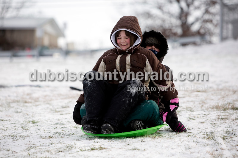 Ariana van den Akker/The Herald<br /> Raya Dollaway of Huntingburg, 10, left, and her sister Rachel, 12, attempted to fit on one saucer while sledding at Niehaus Memorial Park in Huntingburg on Monday morning. All Dubois County schools were closed because of the snow and ice on Monday, though the siblings still had school in the afternoon because they are home schooled.