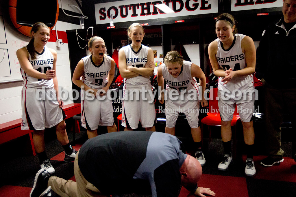 Southridge's Kadie Dearing, left, Kayla Voegerl, Taylor Neukam, Kendyl McKeough and Sydney Altmeyer jokingly jeered at coach Ted O'Brien after he stopped at 79 pushups instead of 80 in the locker room after Monday night's game against Northeast Dubois at Memorial Gym in Huntingburg. O'Brien did the final pushup. The Raiders won 58-26. Ariana van den Akker/The Herald