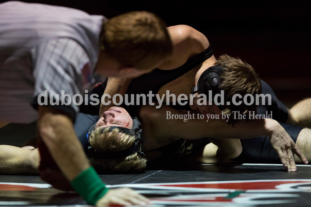 Southridge's Logan Meyerholtz attempted to pin Jasper's Skylar Byrd as the referee, Kevin Huelsman, waited to call the pin, in the 106-pound weight class during Tuesday's match at Memorial Gymnasium in Huntingburg. <br /> Alisha Jucevic/The Herald