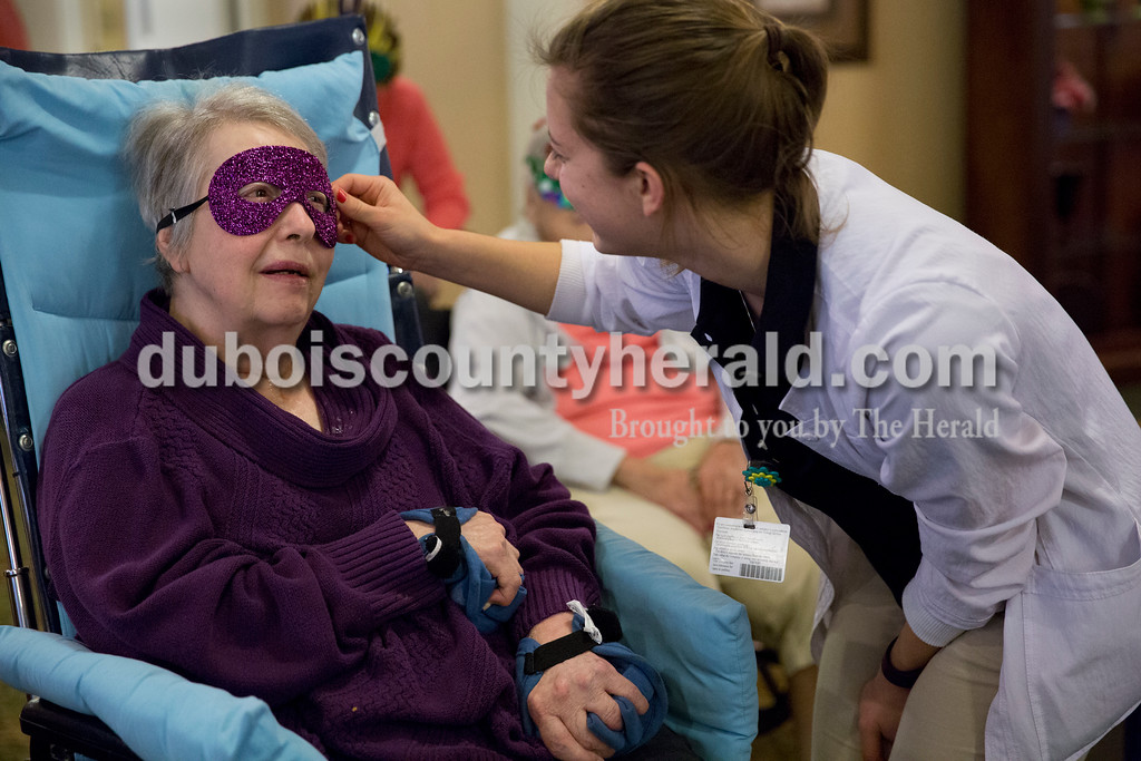 Sarah Ann Jump/The Herald<br /> Kendall Humbert of Dubois adjusted the mask on Shirley Neukam of Jasper before a masquerade mask parade at St. Charles Health Center in Jasper on Friday.