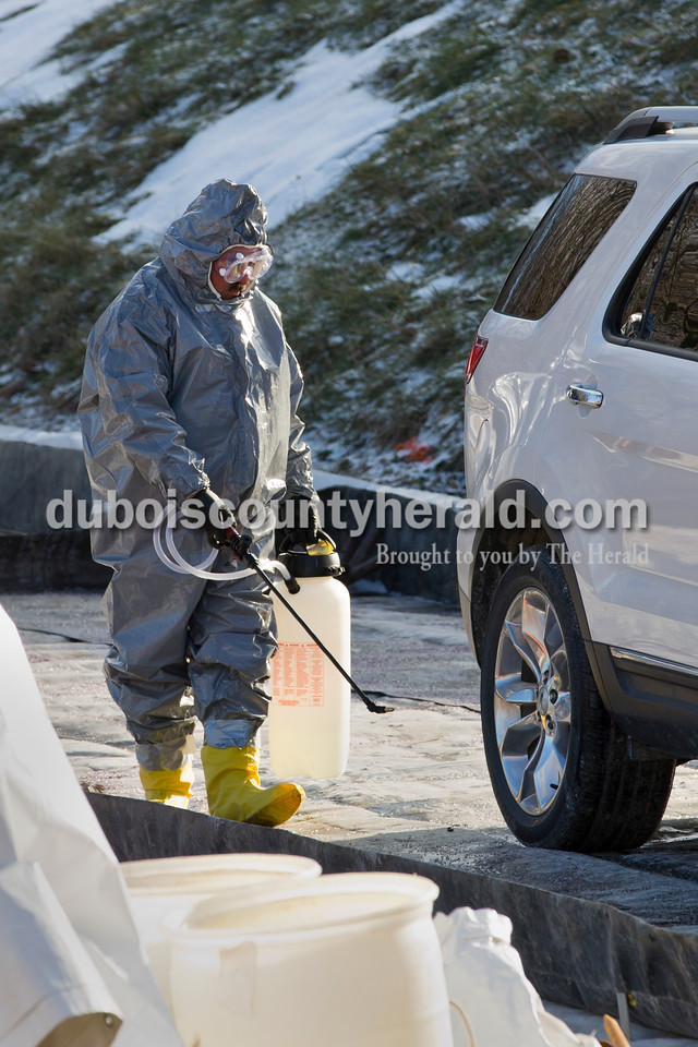 Sarah Ann Jump/The Herald<br /> A worker sprayed a vehicle as part of the decontamination process in order to leave Steve and Dan Kalb's farm in Dubois on Sunday.
