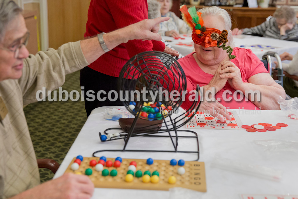 Sarah Ann Jump/The Herald<br /> Jane Flores of Jasper, right, won bingo while volunteer Denny Kreilein of Jasper called numbers during a bingo game following a masquerade mask parade at St. Charles Health Center in Jasper on Friday. Flores won a quarter.