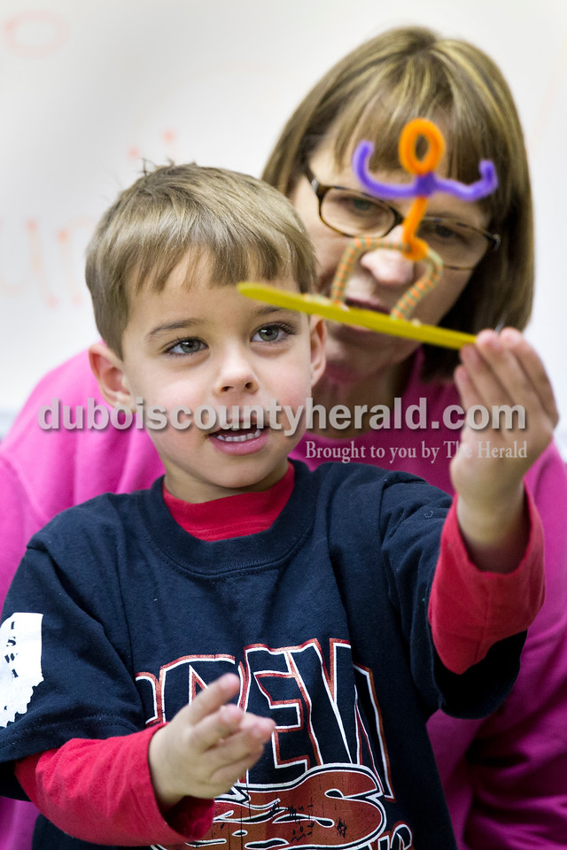 Sarah Ann Jump/The Herald<br /> Rylan Hargett of Huntingburg, 4, held up the pipe cleaner snowboarder he crafted to show his grandmother Marilyn Francis of Huntingburg during the Family Fun Day Open House hosted by the Jasper Arts Center at the Satellite Arts Space in Jasper on Saturday.
