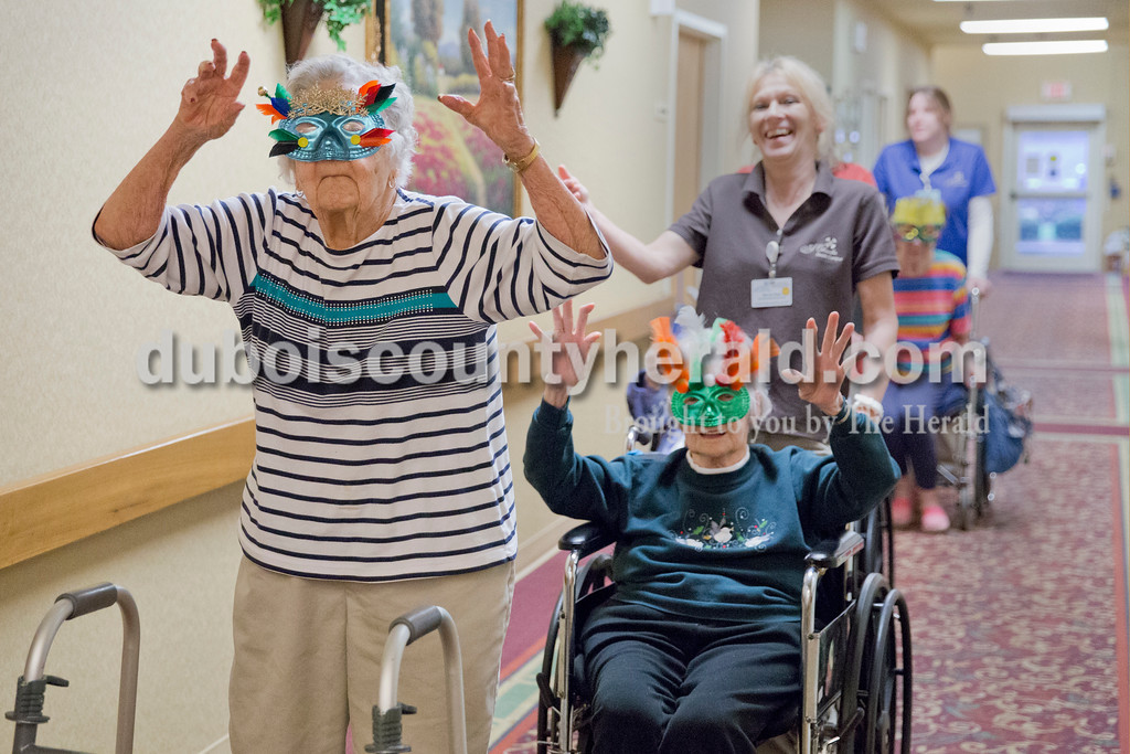 Sarah Ann Jump/The Herald<br /> Florence Hagedorn, left, and Ruby Thimling, both of Jasper, danced as they completed the masquerade mask parade at St. Charles Health Center in Jasper on Friday. The parade ended in the dining room for bingo.