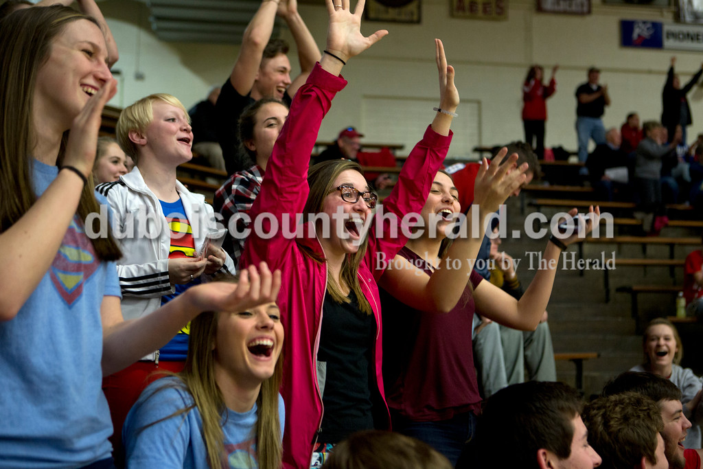 Heritage Hills seniors Shania Mundy, center, and Haley Begle, right, cheered at halftime as a man made a backwards shot into the hoop from the opposite free throw line during the first round of the Class 3A boys basketball sectional against Gibson Southern on Tuesday in Boonville. The Patriots won 55-52. Ariana van den Akker/The Herald