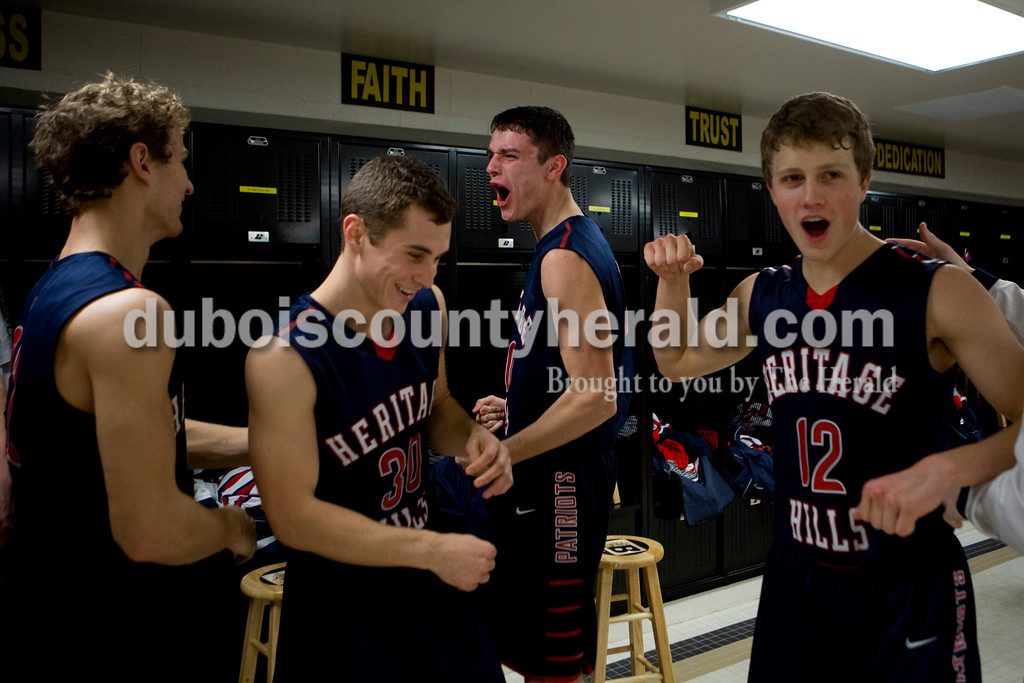 Heritage Hills' Kenton Crews, left, Caleb Mulzer, Gabe Hitz and Alec Meunier celebrated in the locker room after the Patriots won their game against Gibson Southern in the first round of the Class 3A sectional on Tuesday in Boonville. The Patriots won 55-52. Ariana van den Akker/The Herald
