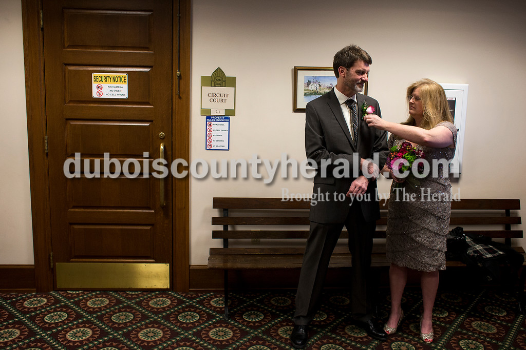 Dave Weatherwax/The Herald<br /> Jeannie Hicks, right, adjusted the corsage on the jacket of her fiancee Greg Ellis, both of Jasper, as the couple waited Monday outside the courtroom at the Dubois County Courthouse before their wedding.