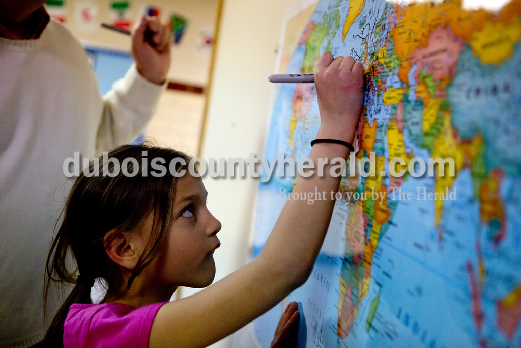 Ariana van den Akker/The Herald<br /> Fifth Street Elementary first-grader Kendall Corbin wrote her initials on a world map near Germany, to show where her ancestors came from during Multicultural Family Fun Night on Monday at the school in Jasper. The program, put on by Fifth Street Elementary and Tenth Street Elementary, featured crafts, activities and games to teach kids about different cultures.