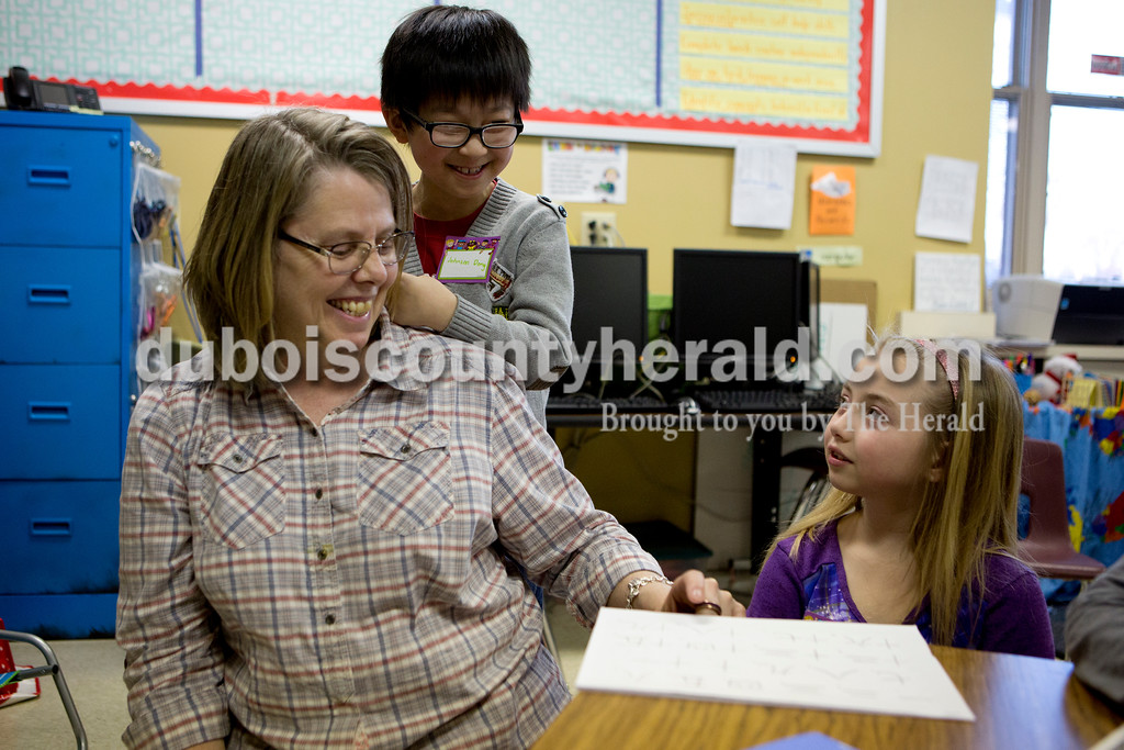 Ariana van den Akker/The Herald<br /> Angie Cox of Jasper, a second grade teacher at Fifth Street Elementary, and second-grader Johnson Dong helped teach second-grader Madyson Hurst the letters one through 20 in Chinese during Multicultural Family Fun Night on Monday at the school in Jasper. The program, put on by Fifth Street Elementary and Tenth Street Elementary, featured crafts, activities and games to teach kids about different cultures.