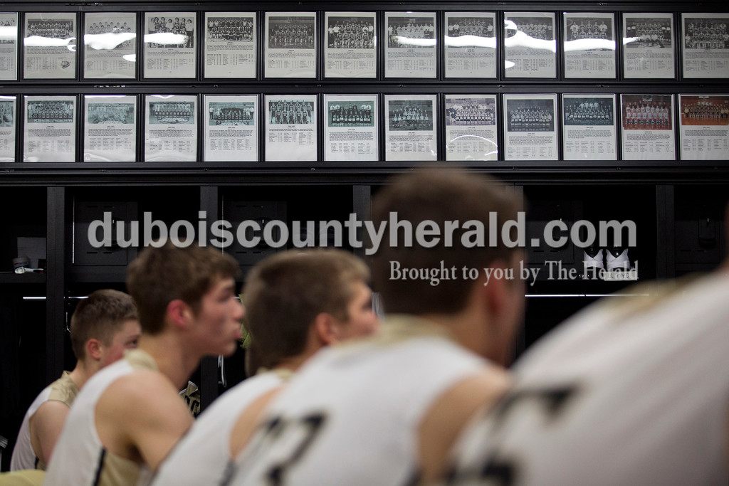 Jasper's head coach Justin Goebel spoke his team before the game against Washington on Jan. 15 in Jasper. Surrounding the cubbies on the top of the locker room walls are framed photographs from each year Jasper High School has had a basketball team. <br /> Alisha Jucevic/The Herald