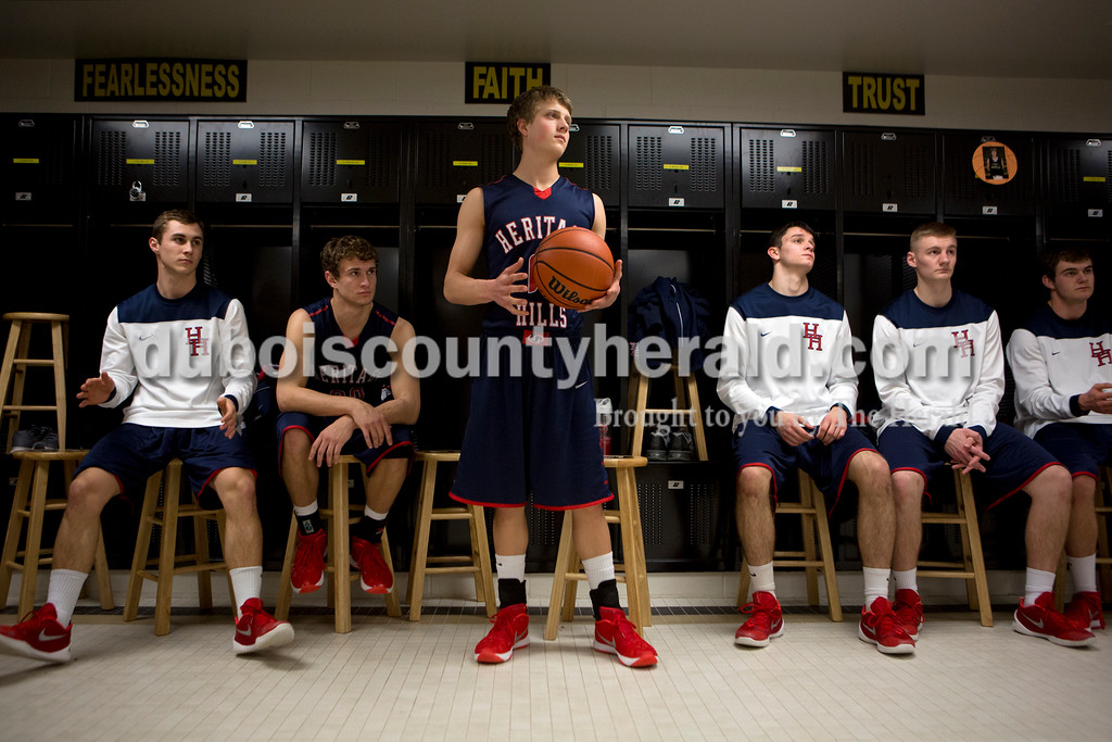 Heritage Hills' Alec Meunier, center, stood in the locker room as he and his teammates listened to coach Matt Sisley before the first round of the Class 3A sectional against Gibson Southern on Tuesday in Boonville. The Patriots won 55-52. Ariana van den Akker/The Herald