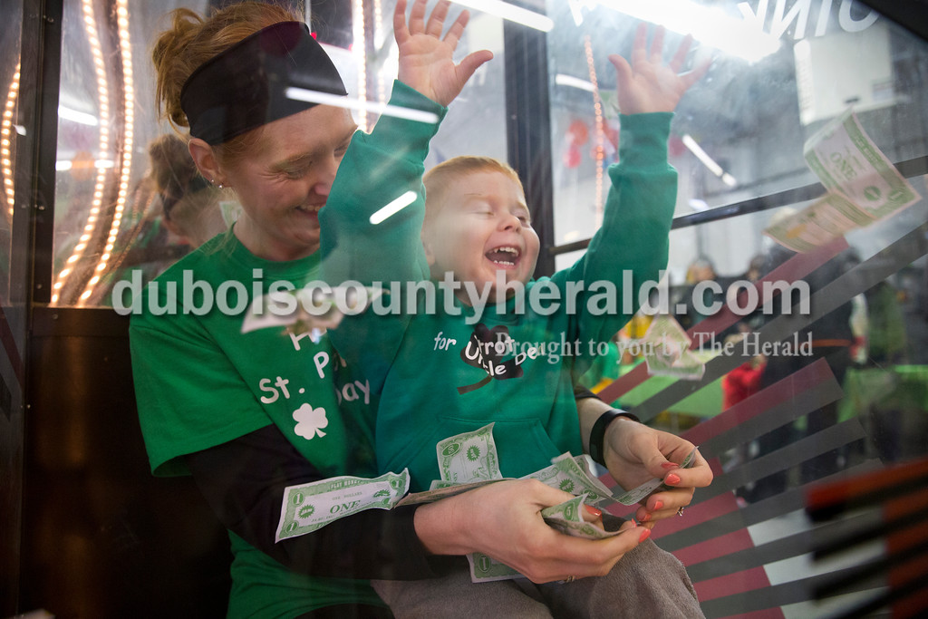 Sarah Ann Jump/The Herald<br /> Lacey Fischer of Celestine held her son Henry, 3, as they tried to catch play money inside the money machine at the Ireland Fire Station during the St. Patrick's Celebration on Saturday.