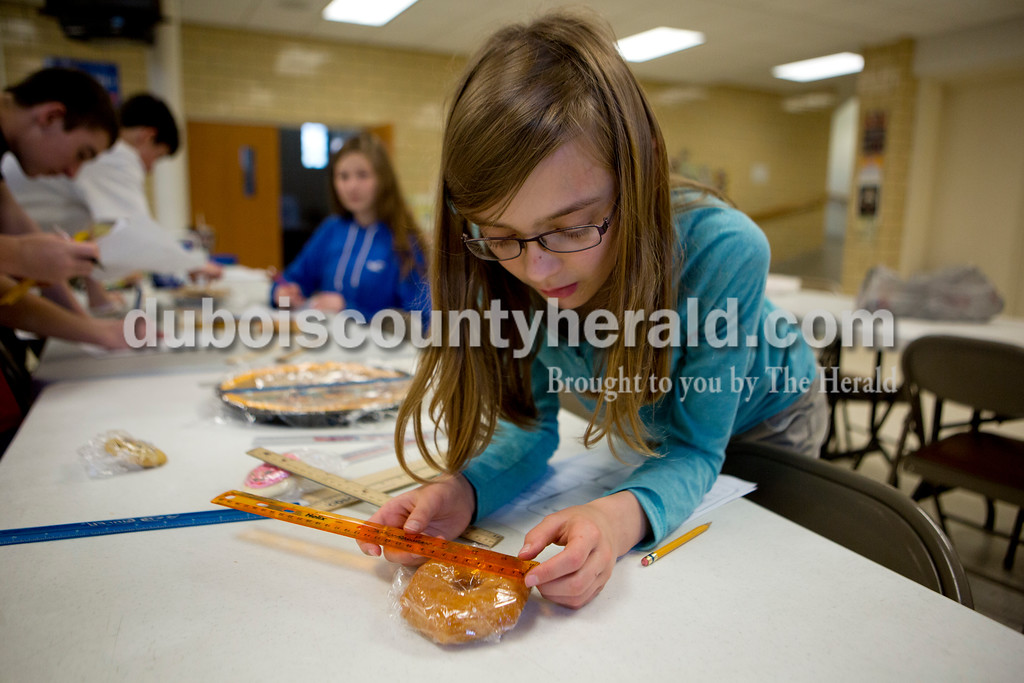 """Ariana van den Akker/The Herald<br /> Holy Trinity Catholic seventh-grader Kiersten Woehler measured the diameter of a doughnut so she could calculate its area and circumference as part of """"Pi Day"""" activities at the school's East Campus on Monday. After calculating, the students feasted on the snacks they measured."""