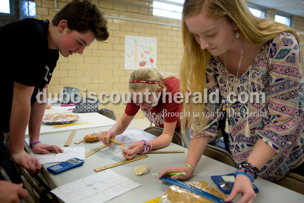 """Ariana van den Akker/The Herald<br /> Holy Trinity Catholic seventh-graders Owen Franks, left, Meredith Heim and Caroline McCance measured the diameters of various circular desserts so they could calculate the area and circumference of each as part of """"Pi Day"""" activities at the school's East Campus on Monday. After calculating, the students feasted on the snacks they measured."""