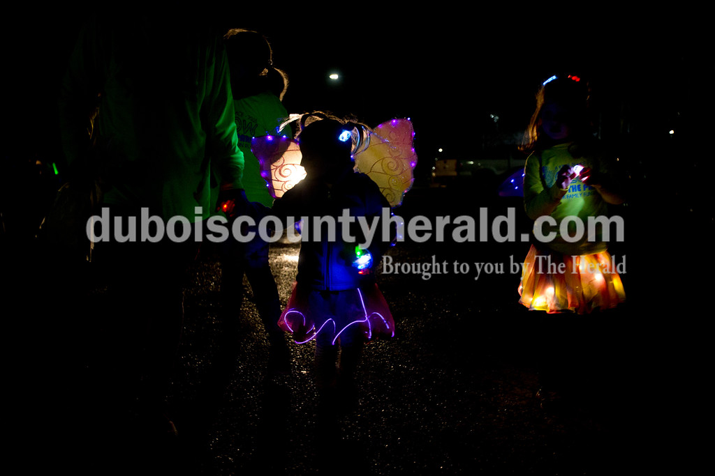 Ariana van den Akker/The Herald<br /> Lily Jones of Jasper, 12, left, held hands with family friend Mya Uebelhor of Huntingburg, 6, as another friend Norah Desser of Jasper, 6, right walked during the Glow in the Park 5K and family fun run on Friday at Huntingburg City Park. The race raised money for A Kid's Place, a non-profit daycare and preschool in Huntingburg.