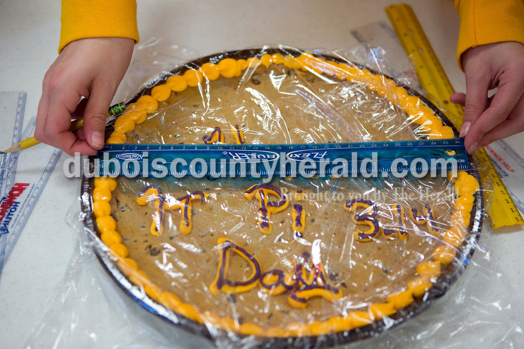 """Ariana van den Akker/The Herald<br /> Holy Trinity Catholic seventh-grader Addison Clauss measured the diameter of a cookie cake so she could calculate its area and circumference as part of """"Pi Day"""" activities at the school's East Campus on Monday. After calculating, the students feasted on the snacks they measured."""