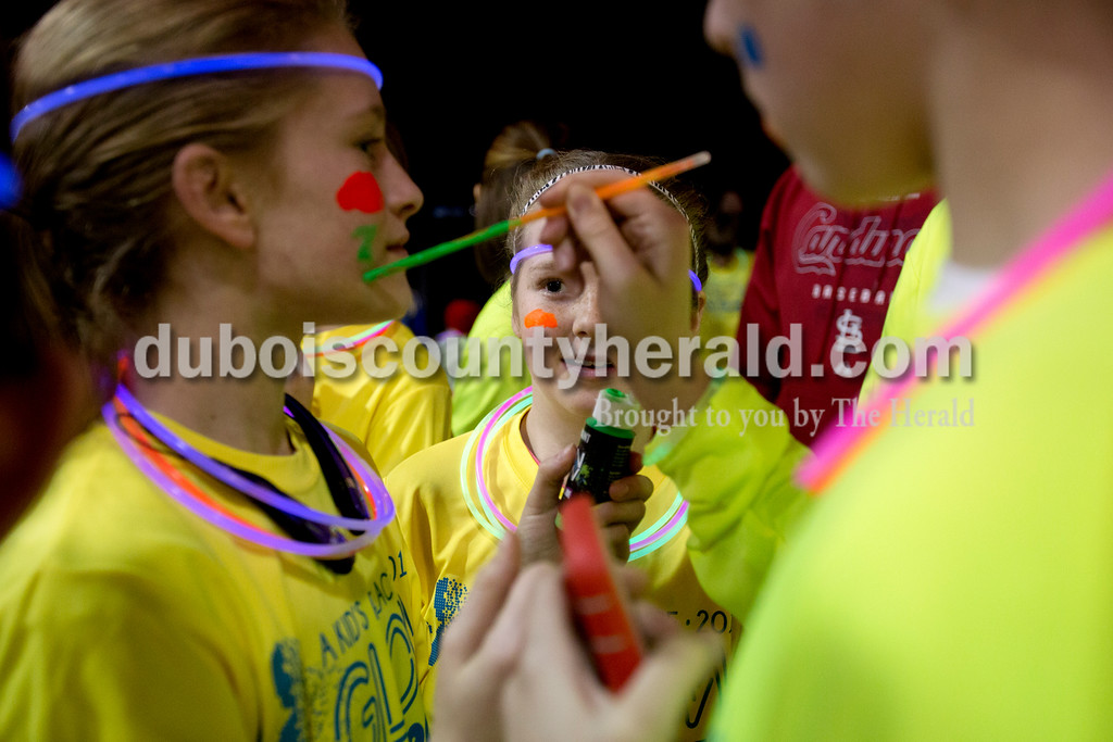 Ariana van den Akker/The Herald<br /> Jenna Kendall of Huntingburg, 11, center, watched Rose Tempel of St. Henry, 13, right, paint her sister Marie Tempel, 11, with neon paint before the Glow in the Park 5K and family fun run on Friday at Huntingburg City Park. The race raised money for A Kid's Place, a non-profit daycare and preschool in Huntingburg. The neon paint lit up under a black light.