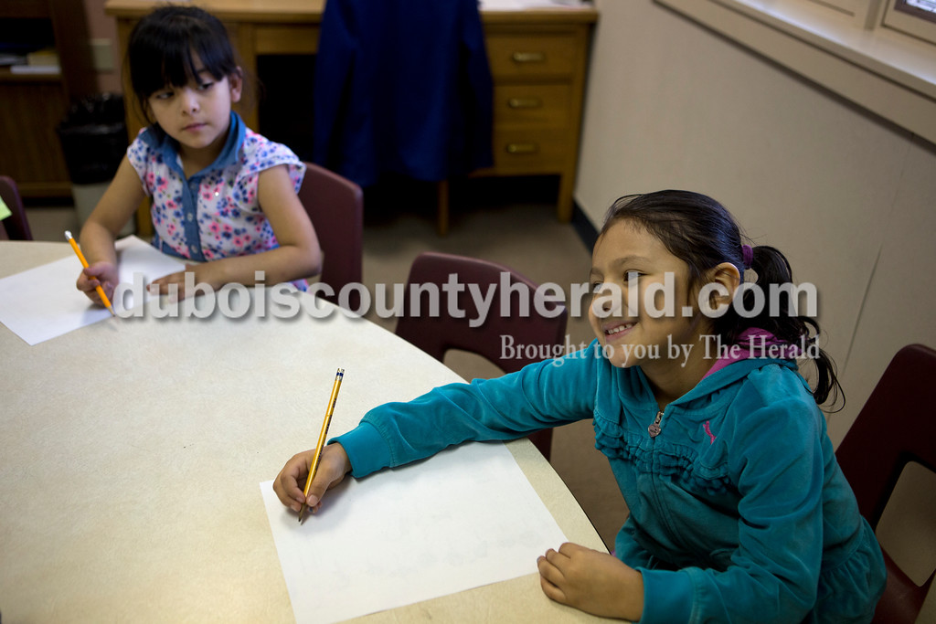 Ariana van den Akker/The Herald<br /> Fifth Street Elementary kindergarteners Karina Salas, left, and Kaylee Ayala worked on writing sentences about what fruit or vegetable they and their classmates liked while working with English Language Learner teacher Lindsey Healy at the school in Jasper on Tuesday morning. Kaylee replied that she likes purple grapes.
