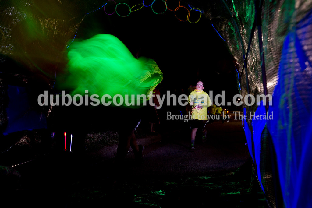 Ariana van den Akker/The Herald<br /> Alex Palma of Huntingburg, 10, ran into a glow tunnel during the Glow in the Park 5K and family fun run on Friday at Huntingburg City Park. The race raised money for A Kid's Place, a non-profit daycare and preschool in Huntingburg. (Eric Vanegas of Huntingburg, 13, is the blur in the foreground).