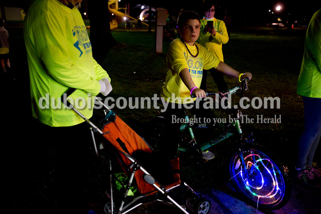 Ariana van den Akker/The Herald<br /> Sawyer Eastridge of  Taswell, 8, waited for the start of the Glow in the Park 5K and family fun run on Friday at Huntingburg City Park. The race raised money for A Kid's Place, a non-profit daycare and preschool in Huntingburg. Sawyer had gotten the bike lights for Christmas and was excited to try them out for the first time.