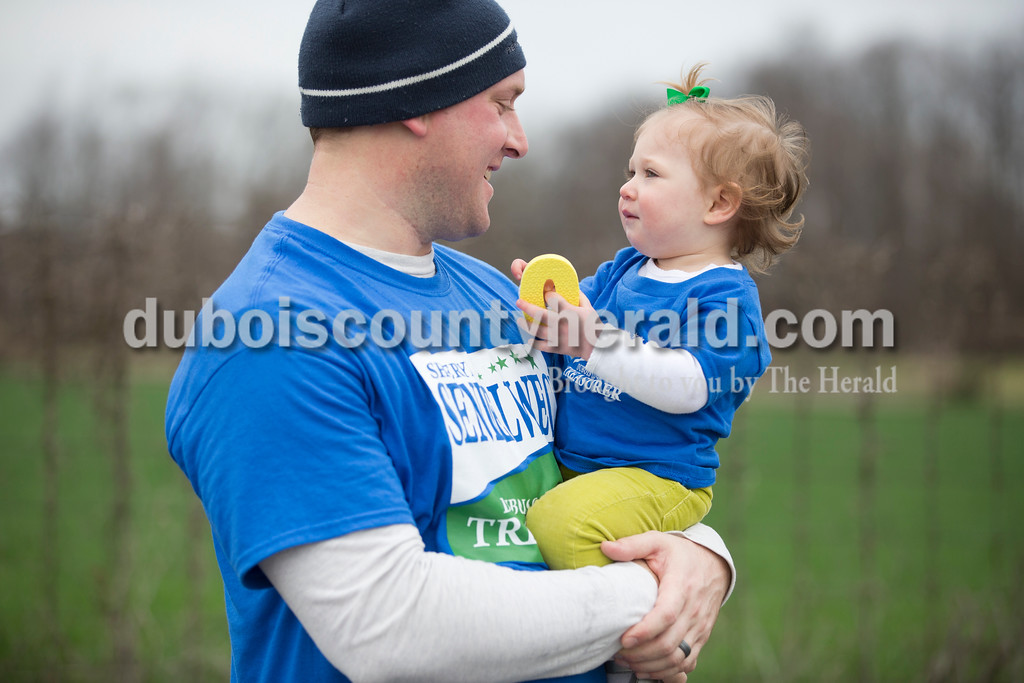 Sarah Ann Jump/The Herald<br /> Luke Schnaus of Ireland held his daughter Kensley, 1, after they completed Saturday's Irish Trot 5K at Ireland Elementary School.