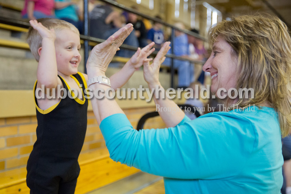 """Sarah Ann Jump/The Herald<br /> Cindy Nicholson of Jasper high-fived her grandson Keegan Martindale of Jasper, 3, before his match during Wednesday's Jasper Youth Wrestling meet at Cabby O'Neill Gymnasium in Jasper. """"I never thought I'd like wrestling, but it's addicting,"""" she said. Nicholson has never missed a wrestling meet for Keegan or his five-year-old brother Landon. At the last meet of the season for Jasper Youth Wrestling, 95 wrestlers in kindergarten through fifth grade competed in three matches each. The wrestlers were matched up based on age, weight and experience."""