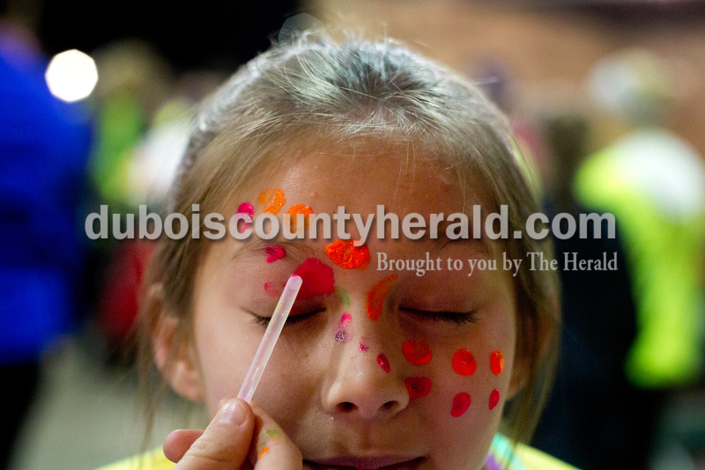 Ariana van den Akker/The Herald<br /> Natilee Wahl of Huntingburg, 11, got her face painted by her friend Kylie Tormohlen of Huntingburg, 11, before the Glow in the Park 5K and family fun run on Friday at Huntingburg City Park. The race raised money for A Kid's Place, a non-profit daycare and preschool in Huntingburg.