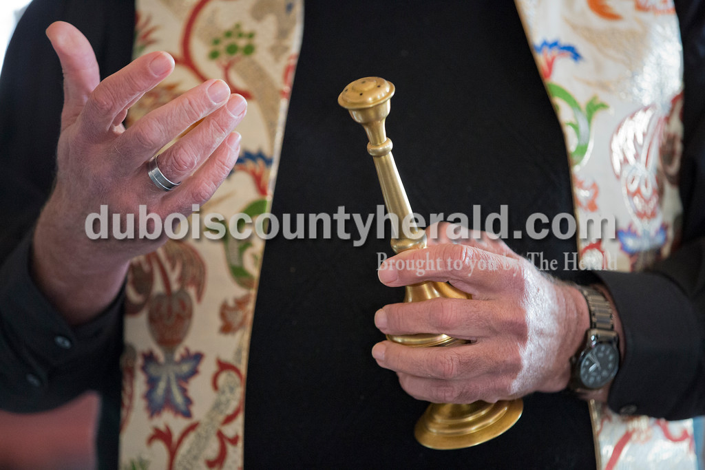 Father John Boeglin of Jasper held an aspergillum, used for sprinkling holy water, after he blessed Patoka Lake Winery in Birdseye on Tuesday, Jan. 12, 2016.