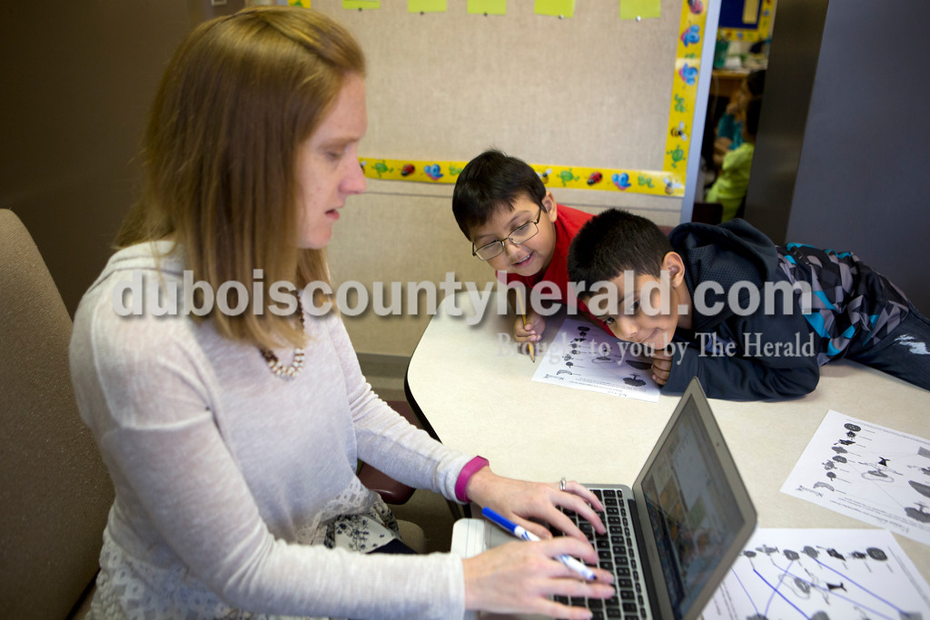 Ariana van den Akker/The Herald<br /> Fifth Street Elementary kindergarteners Anderson Vanegas, center, and Marvin Figueroa tried to sneak a peak at English Language Learner teacher Lindsey Healy's computer as she was finding a photo to show them that grapes grow on vines during a session at the school in Jasper on Tuesday morning.