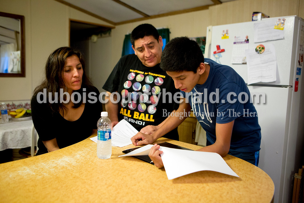 Ariana van den Akker/The Herald<br /> Jaffet Cruz of Huntingburg, 14, explained how a fundraiser for his academic bowl team would work to his parents Yessica Valencia and Wenceslao at their home on Thursday evening. Cruz, an eighth-grader at Southridge Middle School, placed first in the Tri-State Spelling Bee in February, earning a trip to Washington, D.C., to compete in the Scripps National Spelling Bee in April.