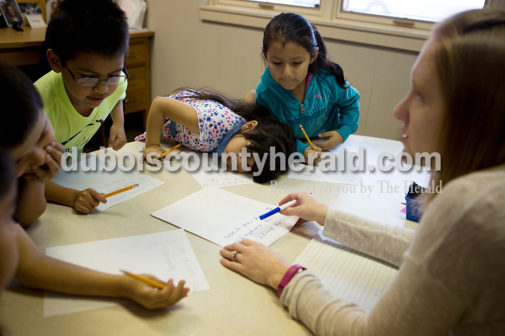 Ariana van den Akker/The Herald<br /> Fifth Street Elementary English Language Learner teacher Lindsey Healy asked kindergartener Alexander Padilla, far left, what his favorite fruit or vegetable is as classmates Dylan Elizarraras, second from left, Karina Salas and Kaylee Ayala awaited his answer while practicing reading and writing at the school in Jasper on Tuesday morning.